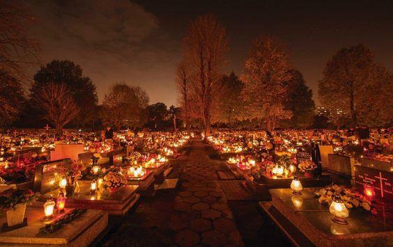 Cemitério à noite com muitas lâmpadas e velas acesas
