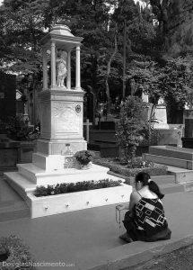 Mulher rezando Terço junto a sepultura