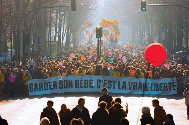 Manifestantes Pró-Vida em grande número seguram grande faixa dizendo que ter filhos é a verdadeira liberdade.