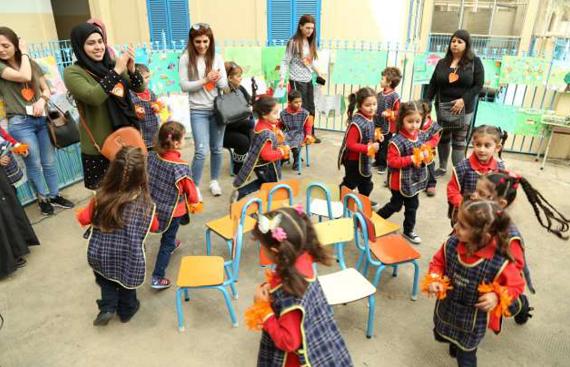 Mães e crianças participam de atividade escolar de dia.
