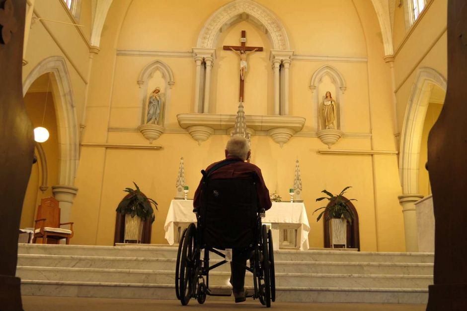 Homem em cadeira de rodas contempla em silêncio o Crucifixo
